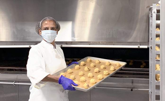 Centerplate staff member Bernitta Green puts cookies in the catering oven