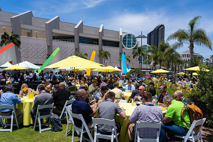 Hundreds of attendees eat lunch in the park outside the Convention Center.