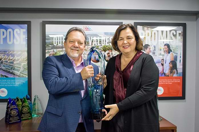 Karen Totaro and CEO Rip Rippetoe stand with a large trophy.