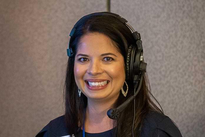 Rita smiles with large headphones on her head.