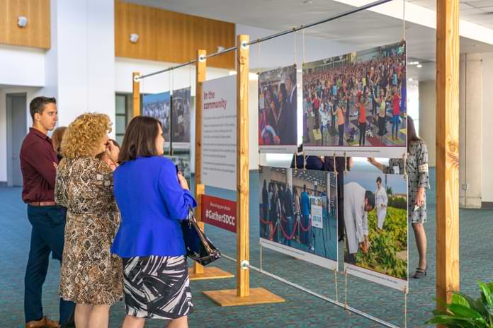 A few people examine a wall of hanging photos of Convention Center community activities