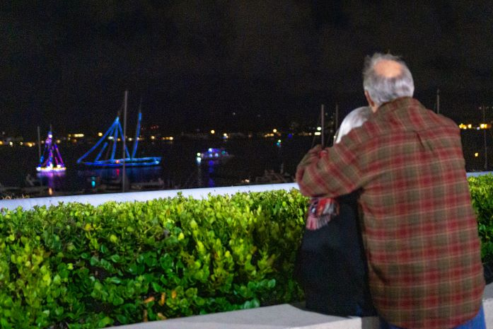 A couple looks onto the bay and a few boats are floating on the water and lit up with lights.