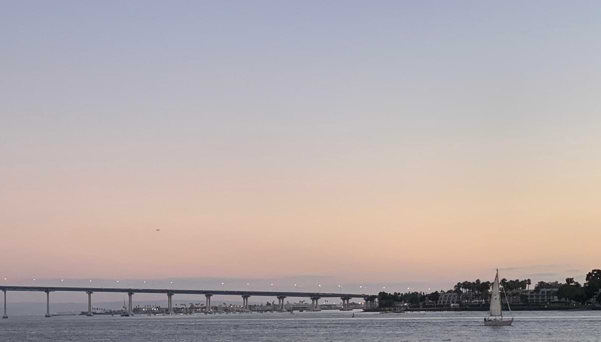 View of the Coronado Bridge and a sailboat on the San Diego Bay